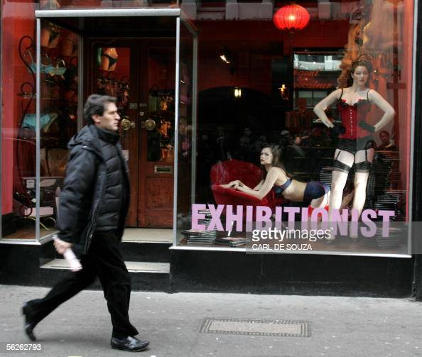 A man walks past models displaying lingerie in a shop window at Agent Provacateur in London 23 November 2005 as the lingerie retail company launches...