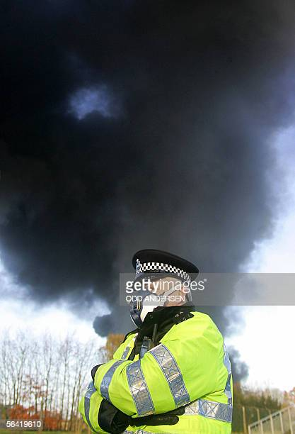 A policeman wearing a protective respiratory mask stands by a cloumn of smoke emanating from the center of an explosion at Buncefield oil depot in...