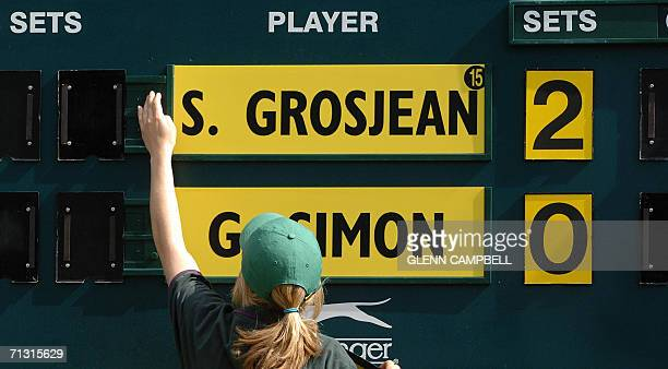 A scoreboard operator is pictured during the games Gilles Simon of France against his compatriot Sebastien Grosjean on the third day of the Wimbledon...