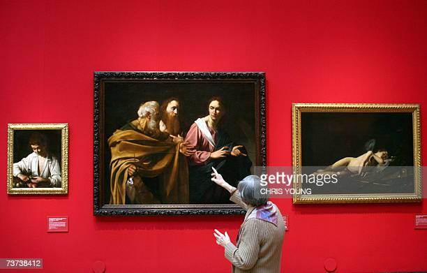 A visitor stands in front of Caravaggio's 'The Calling of Saints Peter and Andrew' as it hangs alongside another of the Italian master's works 'Boy...