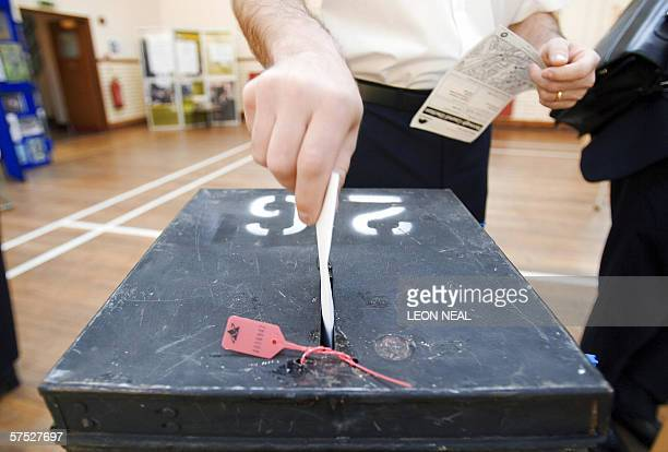 A voter places his voting card in the ballot box at a polling station in Wandsworth in south London 04 May 2006 during the local government elections...