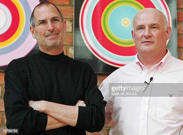 Apple Chief Executive Officer Steve Jobs poses with Eric Nicoli Chief Executive Officer of EMI during a photocall at EMI's offices in London 02 April...