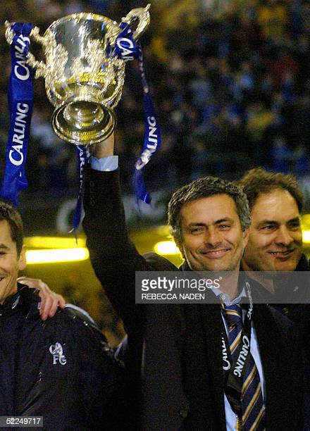 Chelsea's manager Jose Mourinho holds up the Carling Cup trophy after defeating Liverpool in the Carling Cup Final football match at the Millennium...