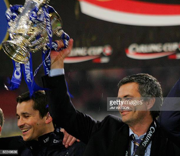 Chelsea's manager Jose Mourinho raises the Carling Cup trophy after defeating Liverpool in ther Carling Cup Final football match at the Millennium...