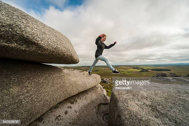 United Kingdom, England, Cornwall, Bodmin Moor, Rough Tor, Rock formation, Girl jumping