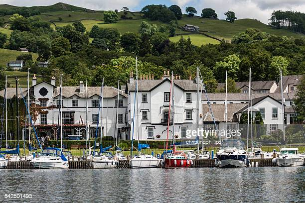 United Kingdom, England, Cumbria, Ambleside, Windermere, Sailboats moored in row at pier with townscape in background