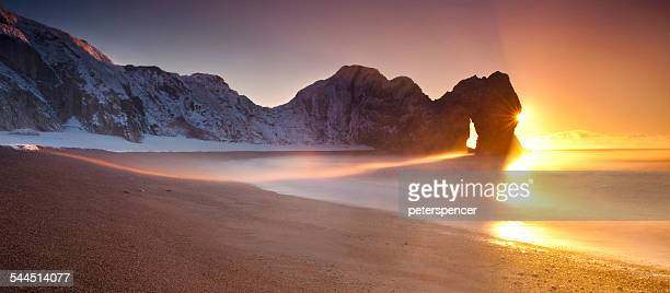 United Kingdom, England, Dorset, Durdle Door and sandy beach at sunrise