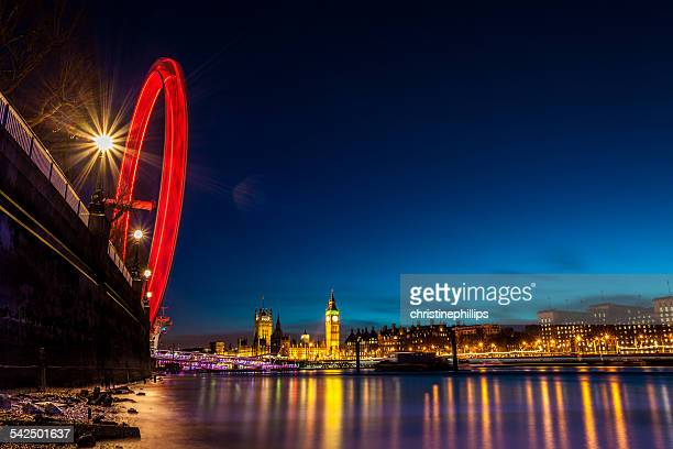 United Kingdom, England, London, London Eye, Westminster Bridge, London Eye in motion and illuminated cityscape reflecting in river