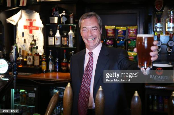 United Kingdom Independence Party leader Nigel Farage holds up a pint of beer that he poured in a pub on May 23 2014 in Benfleet England Early local...