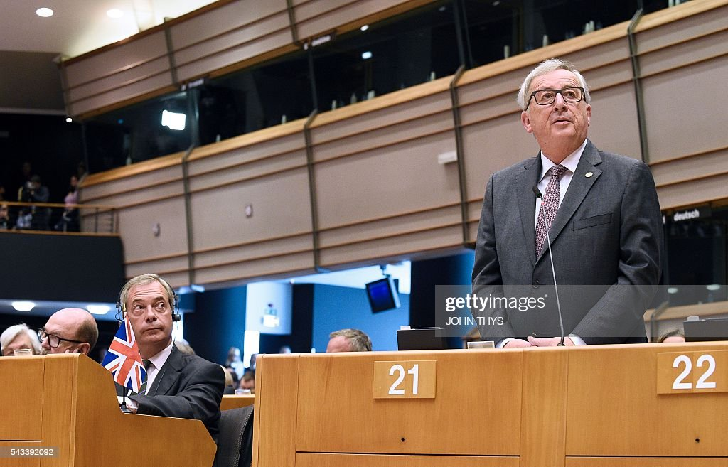 United Kingdom Independence Party (UKIP) leader Nigel Farage (L) looks at European Union Commission President Jean-Claude Juncker as he delivers a speech the European Union headquarters in Brussels on June 28, 2016 ahead of a plenary session. European Commission chief Jean-Claude Juncker called on June 28 on Prime Minister David Cameron to clarify quickly when Britain intends to leave the EU, saying there can be no negotiation on future ties before London formally applies to exit. European leaders gather in Brussels for a crunch two-day summit set to be dominated by Britain's departure from the bloc following its shock referendum last week. / AFP / JOHN