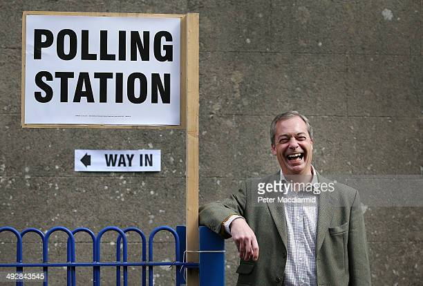 United Kingdom Independence Party leader Nigel Farage poses for photographs as he leaves a polling station on May 22 2014 near Biggin Hill England...
