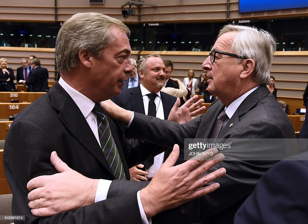 United Kingdom Independence Party (UKIP) leader Nigel Farage (L) reacts as he meets European Union (EU) Commission President Jean-Claude Juncker ahead of a plenary session at the EU headquarters in Brussels on June 28, 2016. European Commission chief Jean-Claude Juncker called on June 28 on Prime Minister David Cameron to clarify quickly when Britain intends to leave the EU, saying there can be no negotiation on future ties before London formally applies to exit. European leaders gather in Brussels for a crunch two-day summit set to be dominated by Britain's departure from the bloc following its shock referendum last week. / AFP / JOHN
