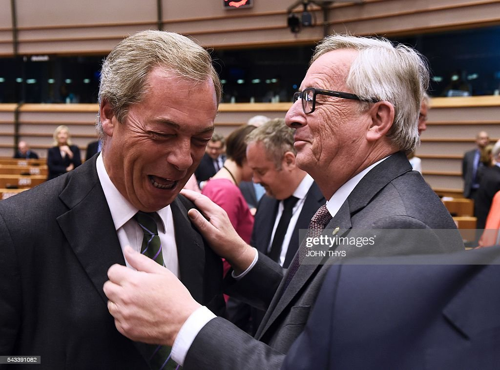 United Kingdom Independence Party (UKIP) leader Nigel Farage (L) reacts as he meets European Union (EU) Commission President Jean Claude Juncker ahead of a plenary session at the EU headquarters in Brussels on June 28, 2016. European Commission chief Jean-Claude Juncker called on June 28 on Prime Minister David Cameron to clarify quickly when Britain intends to leave the EU, saying there can be no negotiation on future ties before London formally applies to exit. European leaders gather in Brussels for a crunch two-day summit set to be dominated by Britain's departure from the bloc following its shock referendum last week. / AFP / JOHN