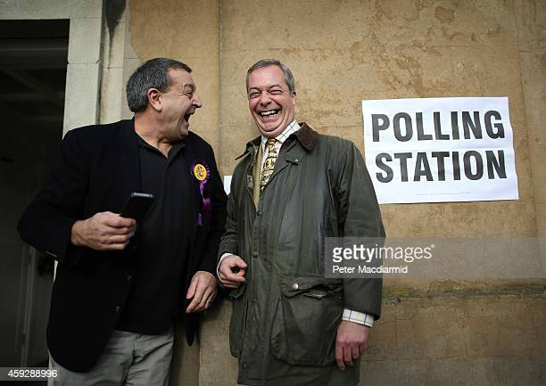 United Kingdom Independence Party leader Nigel Farage shares a joke with party worker Lee Jarvis at a polling station on November 20 2014 in...