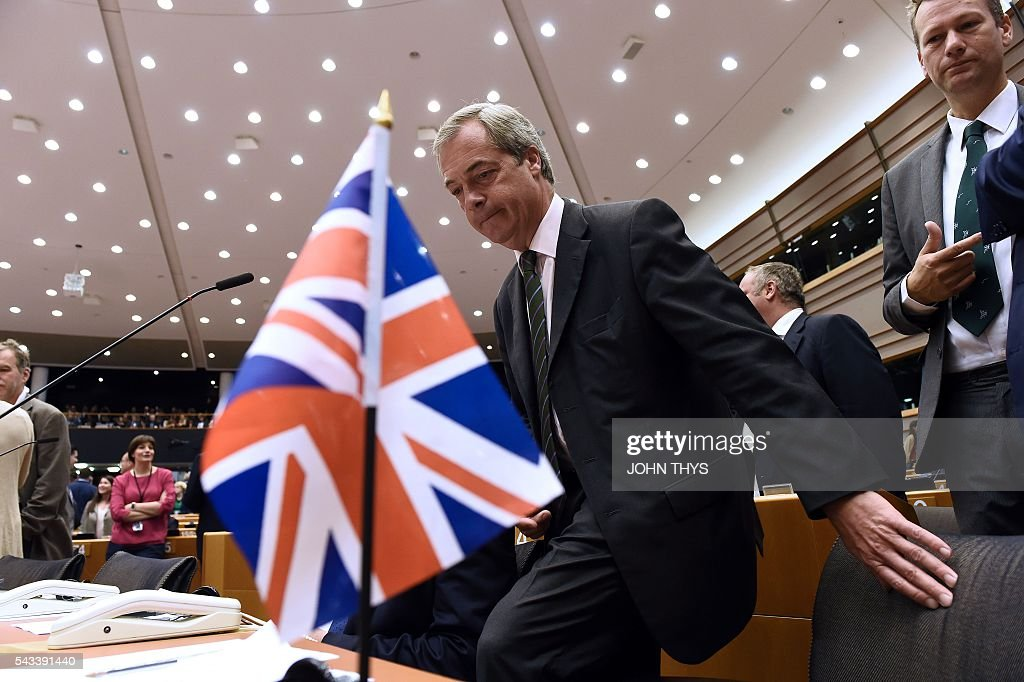 United Kingdom Independence Party (UKIP) leader Nigel Farage (L) sits as he arrives at the European Union (EU) headquarters in Brussels on June 28, 2016 ahead of a plenary session with EU Commission President Jean-Claude Juncker. European Commission chief Jean-Claude Juncker called on June 28 on Prime Minister David Cameron to clarify quickly when Britain intends to leave the EU, saying there can be no negotiation on future ties before London formally applies to exit. European leaders gather in Brussels for a crunch two-day summit set to be dominated by Britain's departure from the bloc following its shock referendum last week. / AFP / JOHN