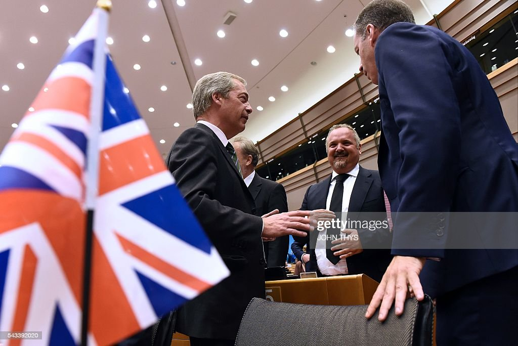 United Kingdom Independence Party (UKIP) leader Nigel Farage (L) speaks as he arrives at European Union (EU) headquarters in Brussels on June 28, 2016 for a meeting with EU Commission President Jean-Claude Juncker ahead of a plenary session. European Commission chief Jean-Claude Juncker called on June 28 on Prime Minister David Cameron to clarify quickly when Britain intends to leave the EU, saying there can be no negotiation on future ties before London formally applies to exit. European leaders gather in Brussels for a crunch two-day summit set to be dominated by Britain's departure from the bloc following its shock referendum last week. / AFP / JOHN