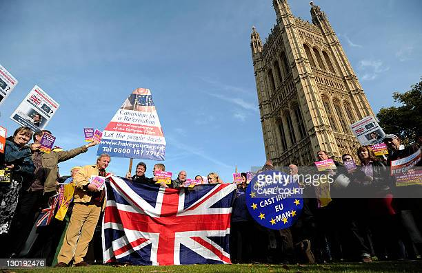 United Kingdom Independence Party supporters hold Union Jack flags and placards as they take part in a demonstration outside the Houses of Parliament...
