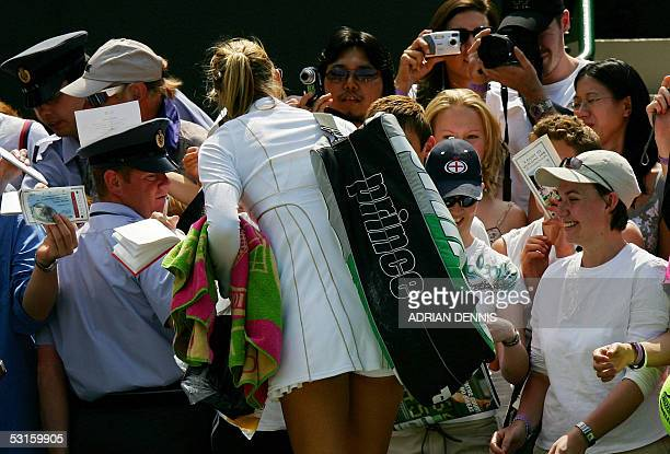Maria Sharapova of Russia signs autographs after defeating Nadia Petrova of Russia during their quarter final match at the 119th Wimbledon Tennis...