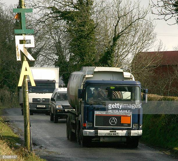 Members of the Police Service of Northern Ireland escort lorries from a house where three people were arrested during a massive security operation...