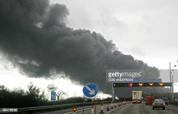 Motorists using the M1 motorway pass through smoke rising from a fierce fire at the center of an explosion at Buncefield oil depot in Hemel Hempstead...