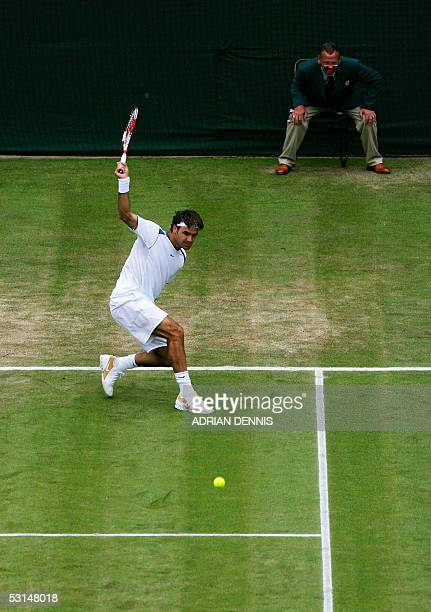 Roger Federer of Switzerland hits a forehand to Nicolas Kiefer of Germany during their match at the 119th Wimbledon Tennis Championships in London 25...