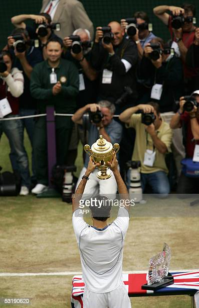Roger Federer of Switzerland holds the trophy after defeating Andy Roddick of US during their men's final match at the 119th Wimbledon Tennis...