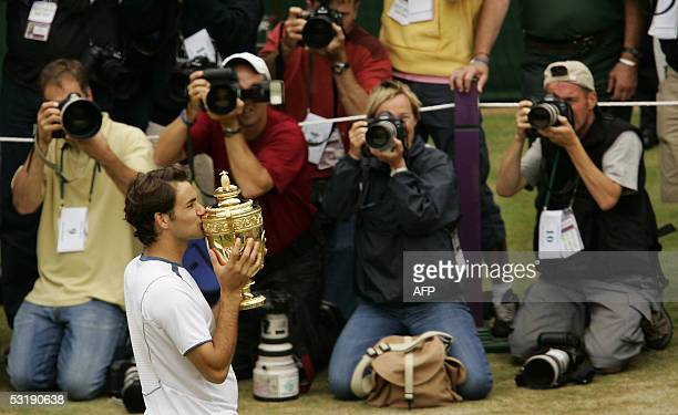 Roger Federer of Switzerland kisses the trophy after defeating Andy Roddick of US during their men's final match at the 119th Wimbledon Tennis...