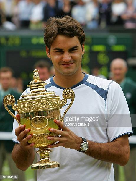 Roger Federer of Switzerland poses with the trophy after defeating Andy Roddick of US after their men's final match at the 119th Wimbledon Tennis...