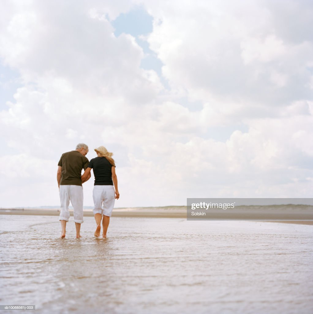 United Kingdom, Rye, Camber Sands, couple holding hands, walking through surf on beach