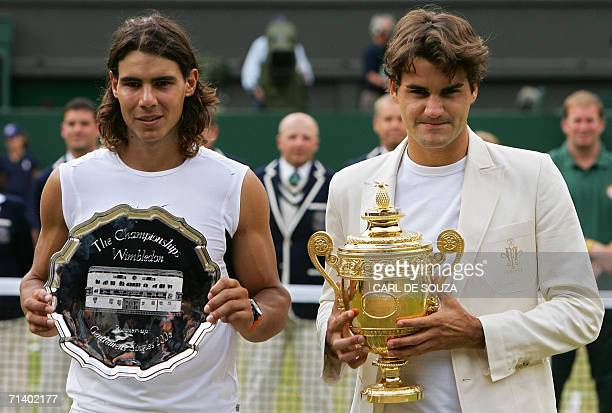 Spain's Rafael Nadal and Switzerland's Roger Federer hold their respective trophies after Federerv celebrates his fourth consecutive Wimbledon...