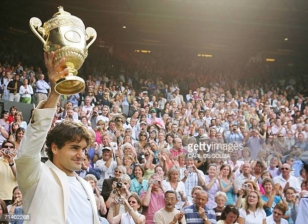 Switzerland's Roger Federer celebrates his fourth consecutive Wimbledon Championships title at the Wimbledon Tennis Championships in Wimbledon in...