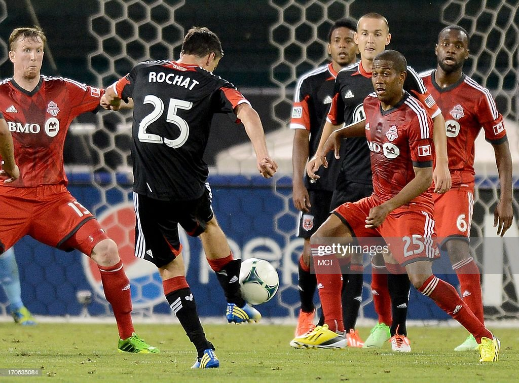 D.C. United midfielder defender Alain Rochat (25) fires a shot into a crowd as Toronto FC defender Steven Caldwell (13) and Toronto FC defender Jeremy Hall (25) prepare to defend in the second half at RFK Stadium in Washington, D.C., Saturday, June 15, 2013. Toronto defeated United, 2-1.
