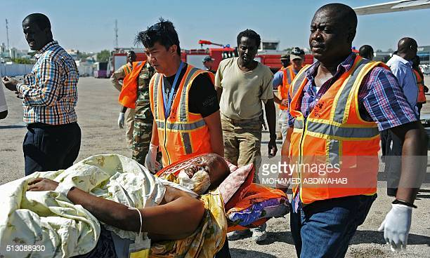 United Nations and AMISOM staff medics help wounded civilians at Mogadishu airport on February 29 after at least 30 people have been killed in twin...