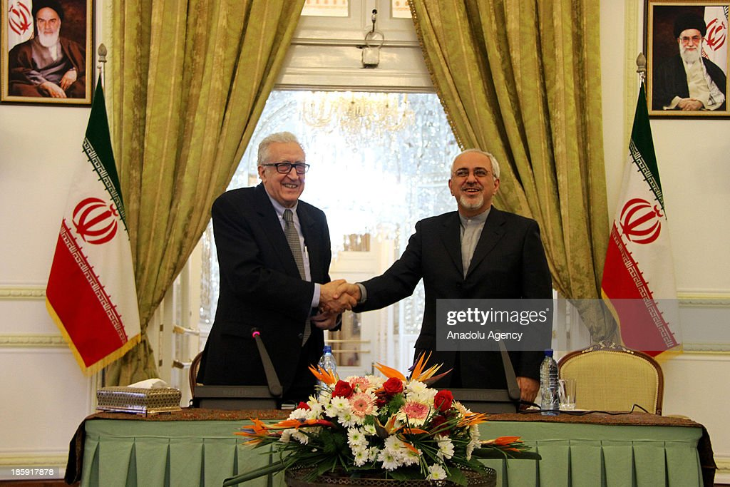 United Nations (UN) Arab League special envoy to Syria Lakhdar Brahimi (L) shakes hand with Iranian Foreign Minister Mohammad Javad Zarif (R) during a joint press conference after their meeting on October 26, 2013 in Tehran, Iran. Brahimi visits Iran as part of his his Middle East tour ahead of the Geneva 2 peace conference.