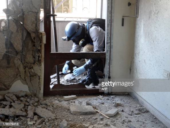 A United Nations arms expert collects samples on August 29 as they inspect the site where rockets had fallen in Damascus' eastern Ghouta suburb...