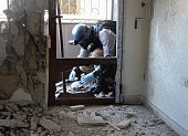 United Nations arms expert collects samples on August 29 as they inspect the site where rockets had fallen in Damascus' eastern Ghouta suburb during...