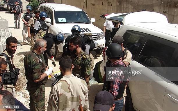 United Nations arms experts and opposition fighters are seen in Damascus' eastern Ghouta suburb on August 29 as UN officials inspect the site where...