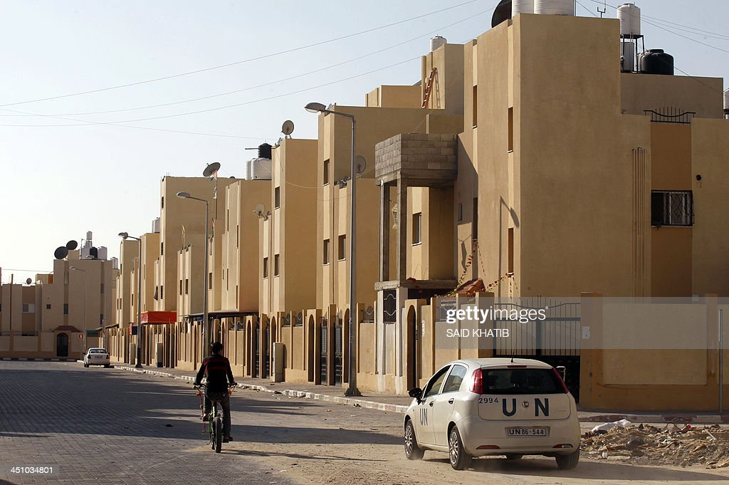A United Nations (UN) car passes in front of new houses which are part of a project funded by the United Nations Relief and Works Agency for Palestine Refugees (UNRWA) in the southern Gaza Strip town of Rafah on November 21, 2013. The UNRWA, which is facing a 36-million dollar deficit, halted 19 out of 20 construction projects in the Hamas-controlled Gaza territory after Israel suspended the entry of all construction materials into Gaza following the discovery of a tunnel by Israeli authorities from the besieged strip into Israel in October.