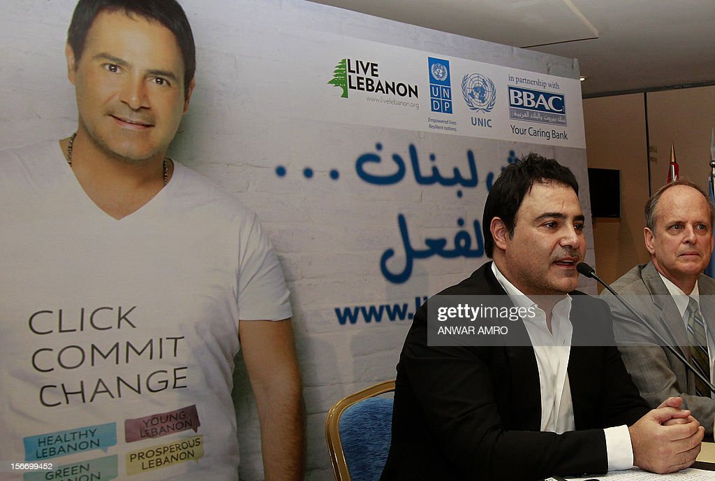 United Nations Development Program (UNDP) representative Robert Watkins (R) sits next to Lebanese singer Assi Hellani upon the latter's appointment as a goodwill ambassador for the 'Live Lebanon' initiative launched by the UNDP, during a press conference at a hotel in Beirut, on November 19, 2012. The initiative aims to improve the living conditions of small communities in Lebanon.