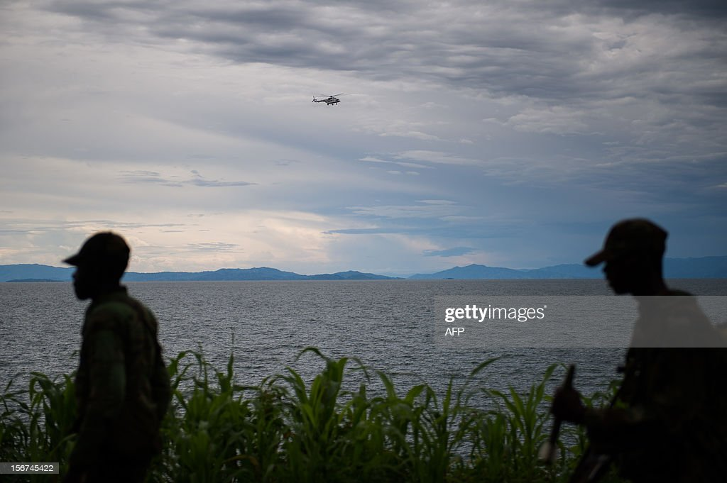 A United Nations helicopter flies over the Lake Kivu as M23 rebels walk along the shore in the city of Goma in the east of the Democratic Republic of the Congo on November 20, 2012. Rebels in the DRC claimed control of the main town of Goma and its airport, in the mineral-rich east, as President Joseph Kabila urged people to defend the country's sovereignty. AFP PHOTO/PHIL MOORE