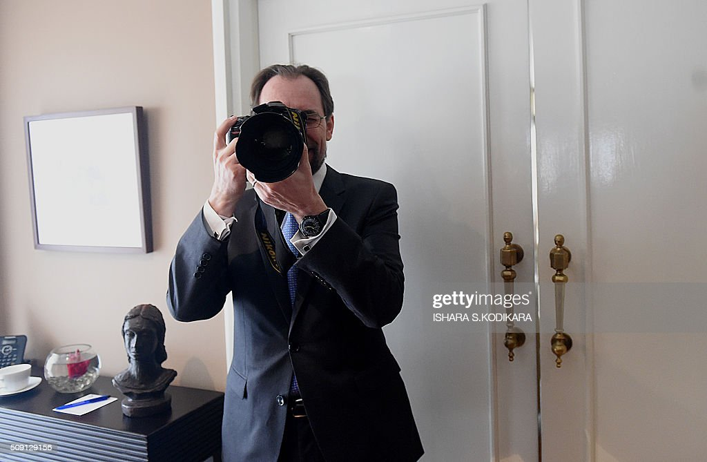 United Nations High Commissioner for Human Rights Zeid Ra'ad Al Hussein checks out the camera of a news photographer covering his meeting with Sri Lankas main opposition leader R. Sampanthan in Colombo on February 9, 2016. Zeid is wrapping up a four-day visit to Sri Lanka to gauge the island's progress in investigating wartime atrocities.. AFP PHOTO/ Ishara S. KODIKARA / AFP / Ishara S.KODIKARA