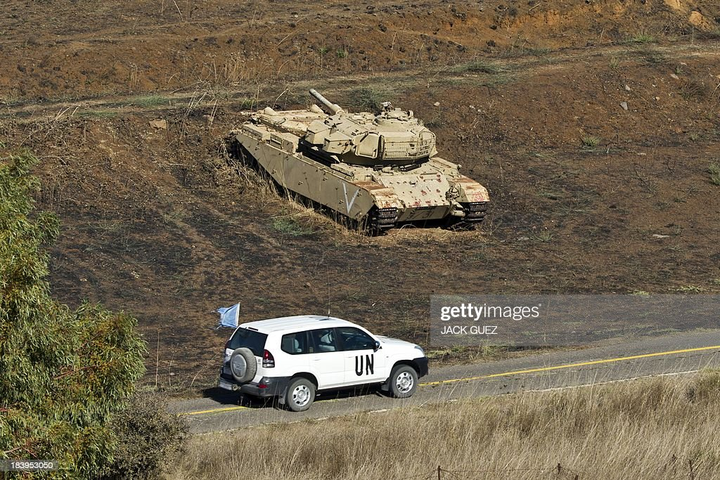 A United Nations (UN) peacekeeper vehicle patrolling the Israeli-Syrian border drives past a deactivated Israeli tank in the Golan Heights, next to the Quneitra checkpoint, on October 10, 2013. The Israeli army fired on October 9, a Tammuz missile across the Syrian border in response to mortar fire from the Syrian at an Israeli military base in the northern Israeli-annexed Golan Heights leaving two soldiers with light wounds.
