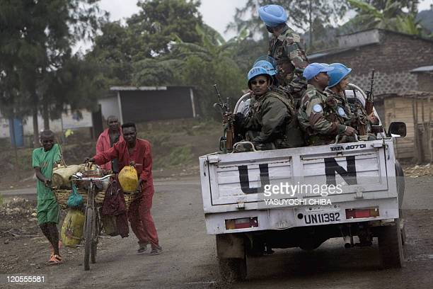 United Nations peacekeepers drive past local residents as they custody an United Nations convoy heading to Rutshuru to relaunch UN operations in the...
