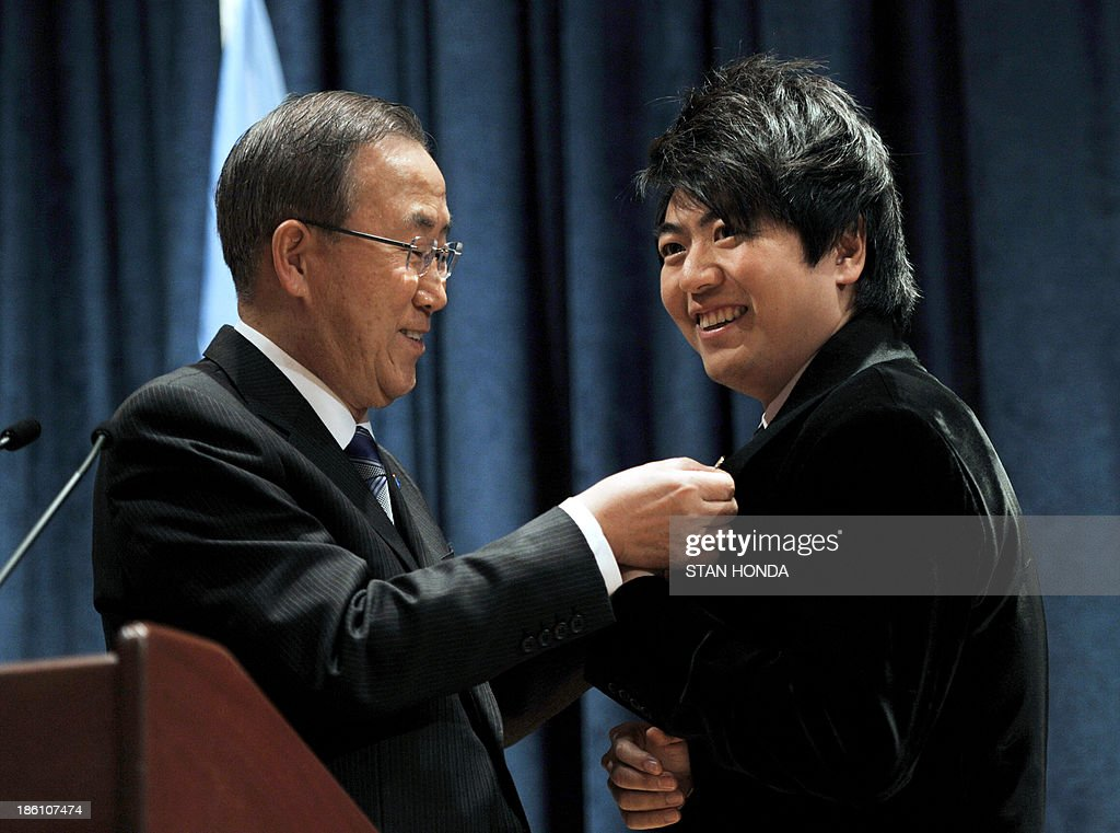United Nations Secretary General Ban Ki-Moon (L) attaches a pin to the lapel of Chinese pianist Lang Lang after naming him a United Nations Messenger of Peace October 28, 2013 at UN headquarters in New York. Lang Lang said Monday he is ready to play in a conflict zone as he was named a UN messenger of peace. The 31-year-old virtuoso said he was 'truly humbled' to become a UN messenger alongside the likes of actors George Clooney and Charlize Theron and Nobel laureate Elie Wiesel. Lang Lang played Chopin's Waltz No 1 for UN leader Ban Ki-moon to mark his new job and was then asked whether he would be ready to go to Syria or another danger zone. 'When the time comes, I would love to do it,' said Lang Lang, who will concentrate on spreading education in his new role. AFP PHOTO/Stan HONDA