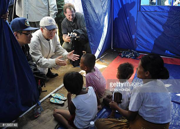 United Nations Secretary General Ban KiMoon talks to a displaced family in their tent May 22 2008 in the Kyondah village Myanmar on a tour to view...