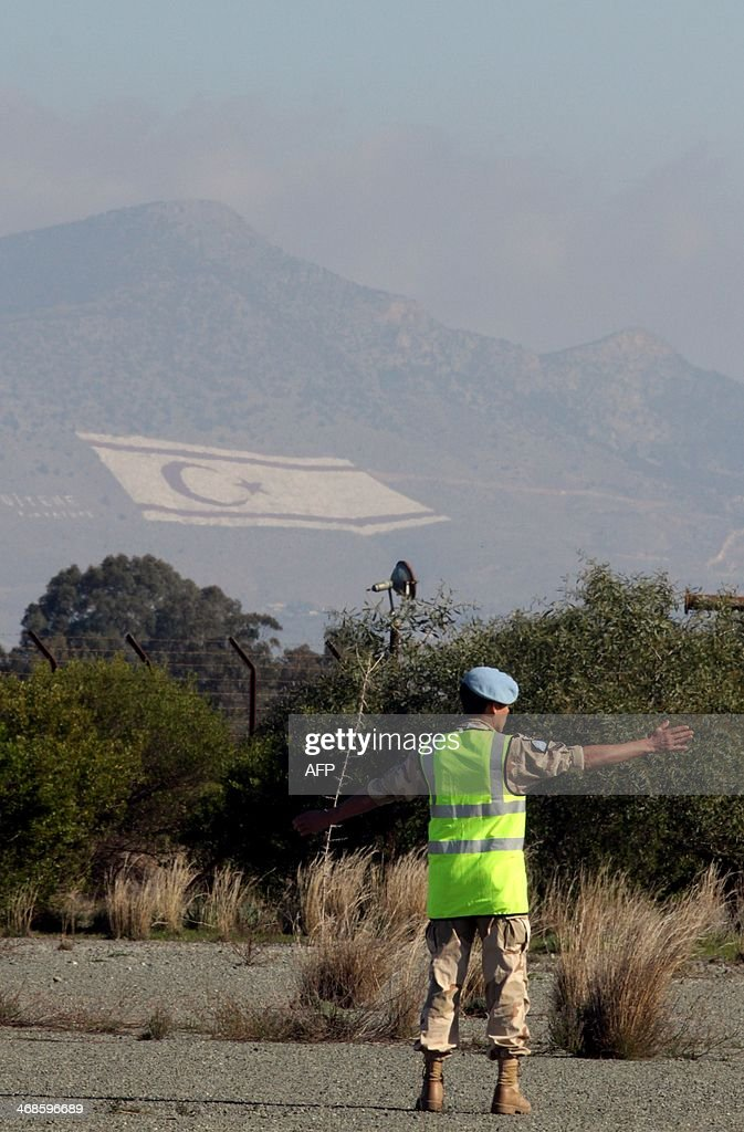 A United Nations soldier stands guard as Greek Cypriot President Anastasiades meets with Turkish Cypriot leader Dervis Eroglu at the now defunct...