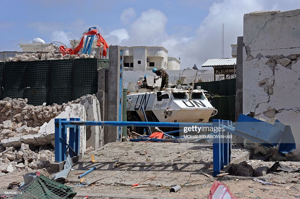 TOPSHOT United Nations soldiers secure a partiallycrumbled perimeter wall following twin car bombings outside the UN's office in Mogadishu on July 26...