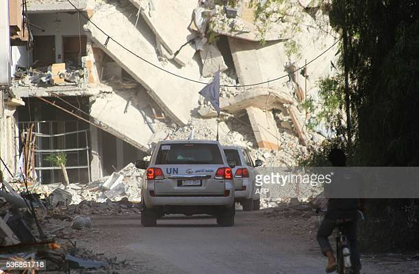 United Nations vehicles drive as an aid convoy entered the rebelheld Syrian town of Daraya southwest of the capital Damascus on June 1 2016 A...