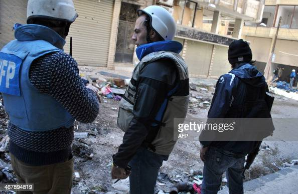 United Nations World Food Programme workers stand near a rebel fighter in a street on February 8 2014 on the second day of a humanitarian mission in...