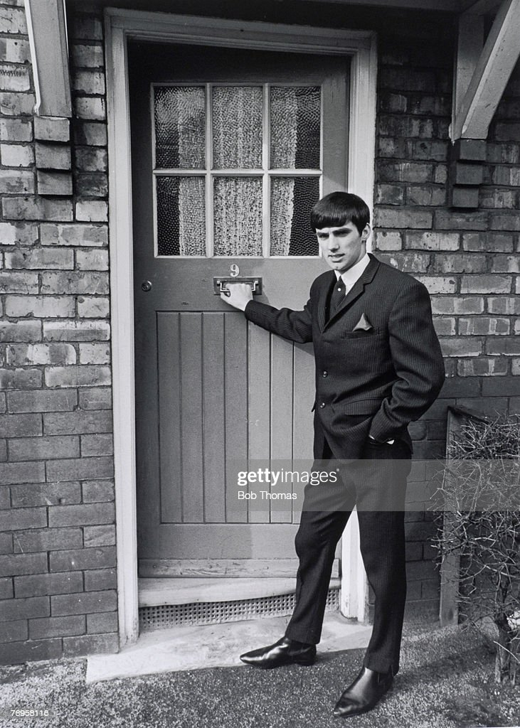 Sport, Football, England, Circa 1964/5, Manchester United & Northern Ireland footballer George Best stands outside the doorway of Mrs Mary Fullaway, his landlady at 9 Aycliffe Avenue, Chorlton-cum-Hardy in Manchester, Seen here wearing a suit and tie and winkle picker shoes